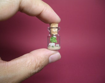 Elephants are in front of the tree in a tiny bottle