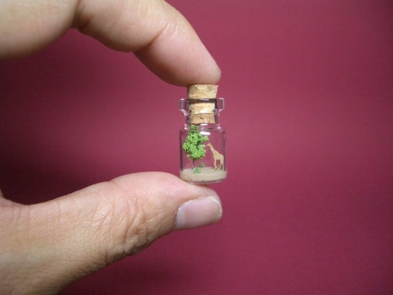 Giraffe is in front of the tree in a tiny bottle