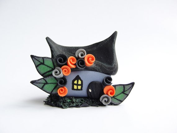 Miniature haunted witch cottage for Halloween made from polymer clay in orange and black
