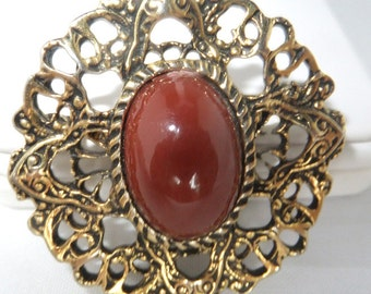 Vintage jewelry brooch in gold tone with faux brick red carnelian
