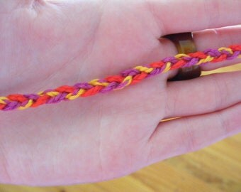 Red, yellow and purple braided friendship band.