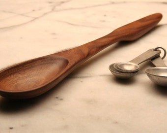 Medium wooden stirring spoon hand made from Walnut wood with ergonomic handle for stirring and mixing