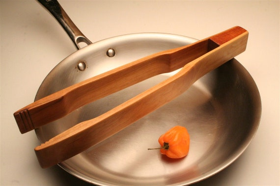 wooden kitchen utensils tongs for turning bacon and serving pasta