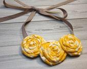 Yellow and white fabric rosettes bib statement necklace