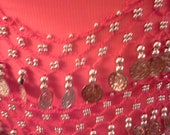 RED tie belt with metal beads & coins attached to crocheted workgoes around waist