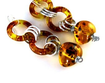 Amber earrings with aluminum hammered rings. Sterling silver ear wire.    Stylish, dangle , long. Modern earrings by Fashion Brand Faina.