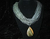 Dark green/gray, beige, and coral sea sediment pendant on green/gray seed bead necklace