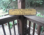 """Scripture sign, wood,primitive sign """"Give us this day our daily bread""""Distressed,primitive, rustic look yellow, with black trim, woodwork"""