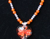 Necklace and Earrings Set: Beautiful blown glass heart with orange flowers in the center with natural carnelian and quartz