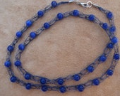 Electric blue cats eye glass beads on dark blue wire.  22 inch length.