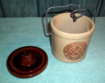 "Vintage Crock with a Lid ""The Great Seal of the United States of America"" printed on the front  side."
