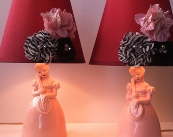 A Pair of Figural Pink Pottery Lamps Girl Playing Lute With Burgundy Lamp Shades 1930's