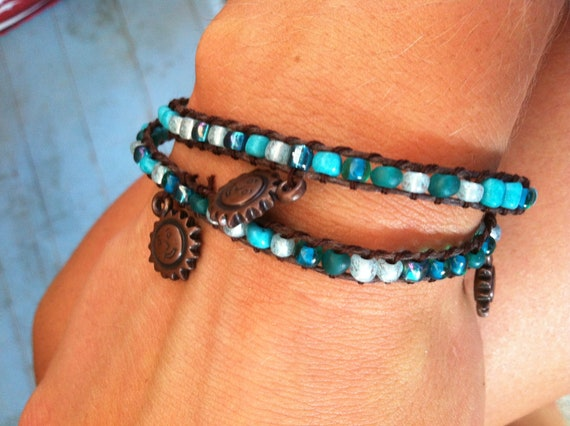 Turquoise beaded bracelet with brown cord and bronze sun charms. 2x wrap around