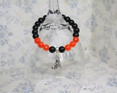 Elasticated black onyx and faceted watermelon ruby beaded bracelet with witch charm