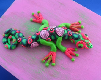 Rectangular wood box with distressed pink and green stenciled finish.Bright green and pink polymer clay lizard on top