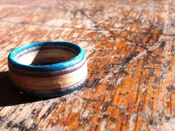 Rings with a light blue stripe hand cut from skateboard decks