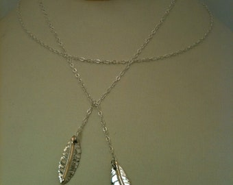 Sterling silver/14kt gold long feather necklace.