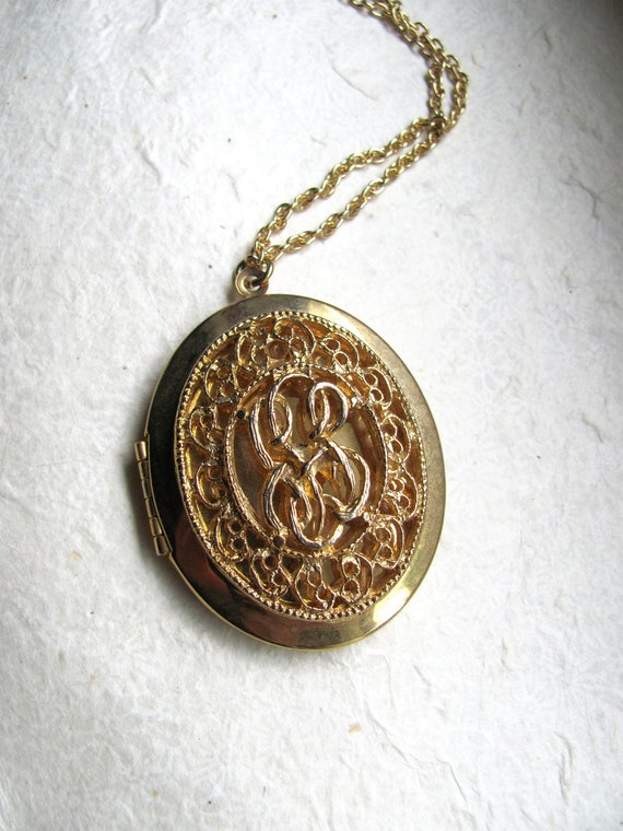 Oversized vintage gold tone oval locket, with filigree embellishment on long chain, by Park Lane