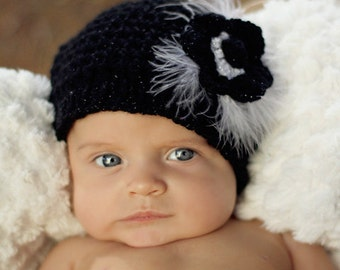 Crochet baby hat with flower and feathers