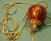 One-of-a-kind pendant necklace of goldcolor metal chain and swirled brown genuin tested 1940s bakelite nut-formed bead with brass details