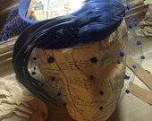 Blue net and feathers hat.