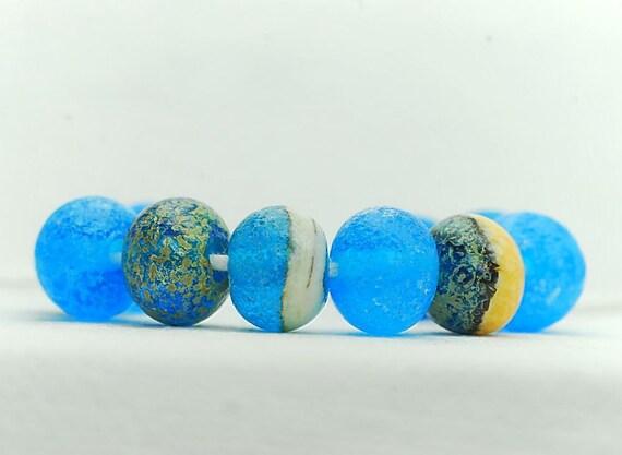 Organic lampwork bead set (11),  fossilized donut, sea blue, ivory, sea green, rustic. SRA