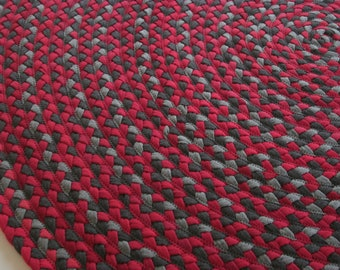 dark red, gray and charcoal hand braided rug created from cotton jersey