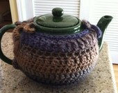 Green ceramic teapot and handmade cozy