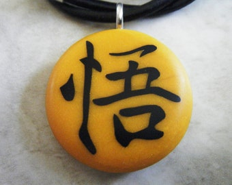"Japanese kanji symbol ""ENLIGHTENMENT""  hand carved on a polymer clay orange pearl color background. Comes with a FREE necklace"