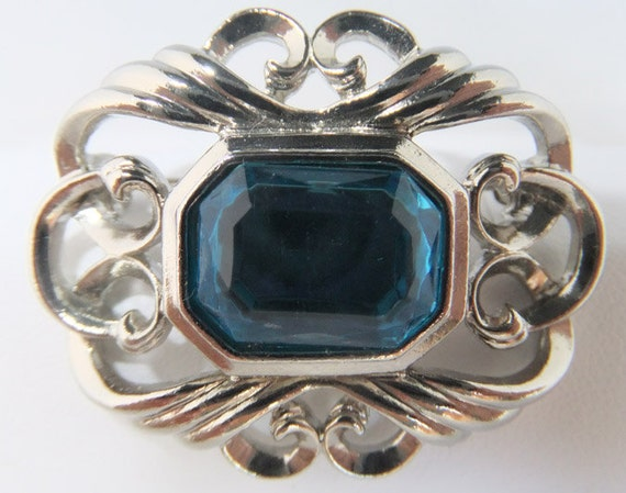 Vintage jewelry brooch by Avon in silver tone with huge faceted faux blue topaz brooch