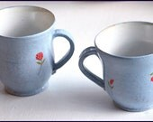 Two pale blue mugs, decorated with red flowers