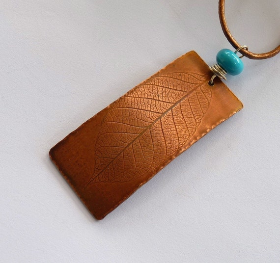 Copper leaf pendant,  turquoise glass bead, leather thong, matching earrings.
