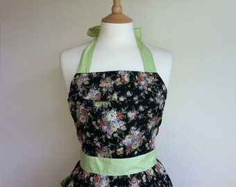 Retro apron with ruffles, floral pattern on a black fabric, 1950s vintage inspired.