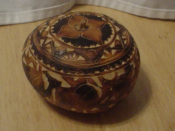 Carved peruvian gourd vessel with men and animals portrayed