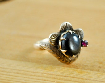 Vintage 14 karat Gold Ring with Oval Black Star Sapphire and Garnet, approximately U.S. size 7, gold floral setting