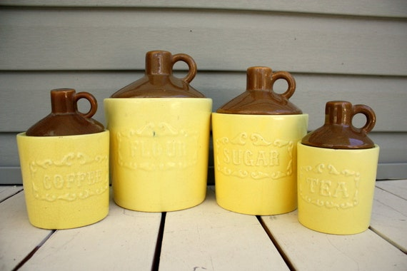 1950s lemon yellow pottery kitchen canisters set. Moonshine jug style
