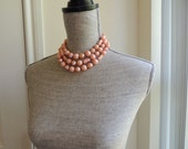 vintage 1950s coral pink salmon beaded necklace. multi strand. triple strand. high fashion. mad men. design. mid century