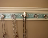 "Jewelry organizer. This necklace rack/ wall organizer has 5 knobs on off white w/ teal embossed background 15 "" beautiful decor & storage"