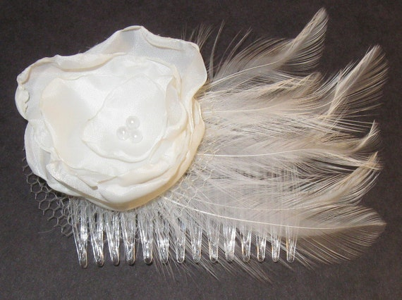 Small white flower fascinator with white feathers, pearls, and netting on a clear comb