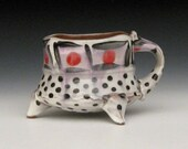 red dot pink and black polka dotted mug with funky feet