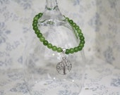 Elasticated green peridot bracelet with tree of life charm