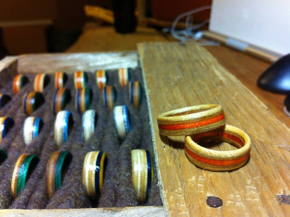 Rings with an orange stripe made from skateboard decks