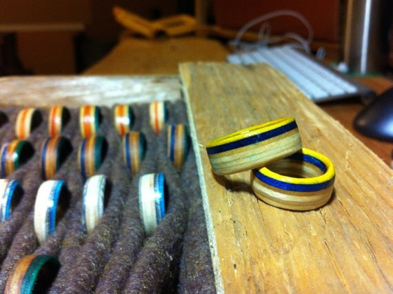 Rings with a blue & yellow stripe hand cut from skateboard decks