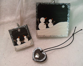 Snowmen and heart ornaments. Set of three handmade and painted wood. 2 snowmen ornaments, 1 heart. Silver glitter.