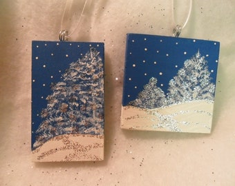 Blue and White ornaments. Set of two. Handpainted on wood. Snow covered pines against snowy sky. Blue and white,with silver glitter. Gift