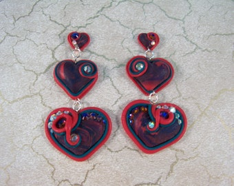 Asymmetrical dangly polymer clay heart earrings with Swarovski crystals.