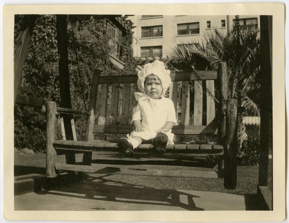 1920s Chubby Faced Cutie with Big Bonnet Sitting on Porch Swing - snapshot 485
