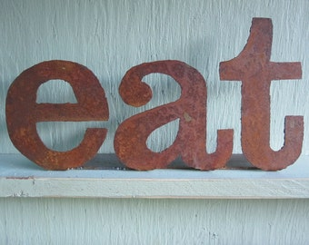 "Metal ""eat"" sign on stand"