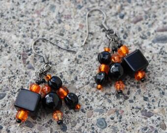 Beaded orange and black cluster earrings