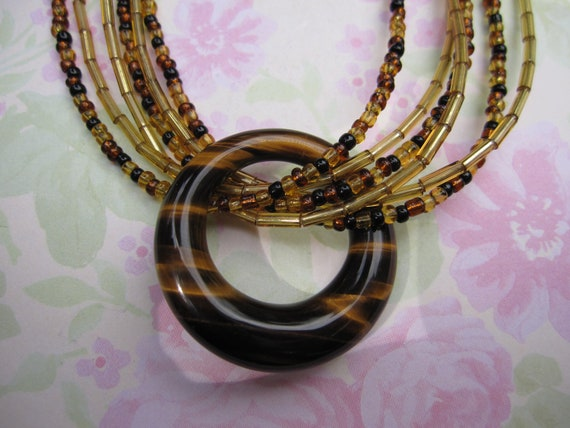 Beautiful black, brown, gold color seed beads and gold color tube bead necklace with round faux tortoise shell glass ring.